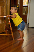 MR / Schenectady, NY. One of a sequence of photographs showing an infant (girl, 10 months, African American & Caucasian) in her pre-walking stage, using a kitchen chair as support as she practises moving from a sitting position to a standing position and back. Here, she laughs as she fully stands up. MR: Dal4. ID: AL-HD. © Ellen B. Senisi