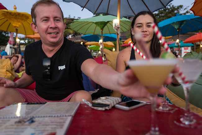 6 DECEMBER, 2019 BALI, INDONESIA: Kane James (35) and Jade Tiedeman (35) from Darwin enjoying a cocktail at sunset on Masari Beach, Seminyak in Bali. There has been a levelling out of Australian tourist numbers to Bali in recent times and tastes are changing regarding what people want from their holiday. Picture by Graham Crouch/The Australian