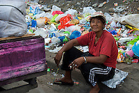 Sorting out rubbish for recycling Slum area Manila from the Car Window, Philippines