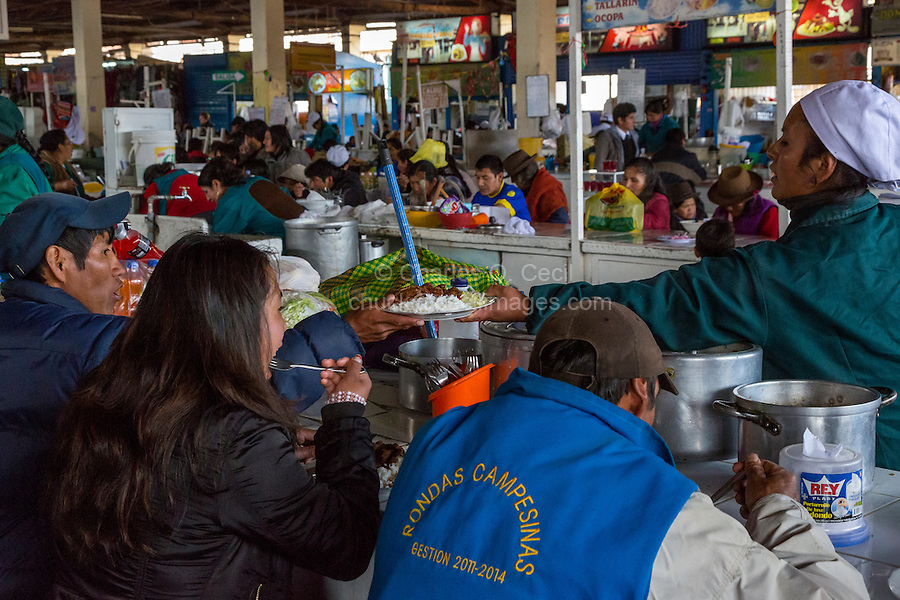Peru, Cusco, San Pedro Market.  Cook Passing Lunch to a Customer Eating in the Food Court Area of the Market.