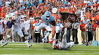 CHAPEL HILL, NC - SEPTEMBER 28: Javonte Williams #25 of the University of North Carolina jumps over K'Von Wallace #12 of Clemson University during a game between Clemson University and University of North Carolina at Kenan Memorial Stadium on September 28, 2019 in Chapel Hill, North Carolina.