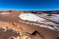 Atacama Desert road surrounded by salt and the beautiful red dunes of El Valle de la Luna (Moon Valley), under a blue sky, San Pedro de Atacama, Chile