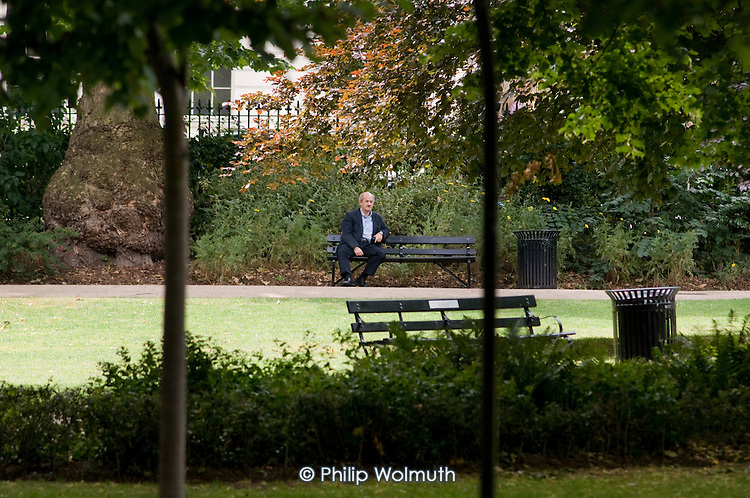 A man sits on a bench in Russell Square, London.