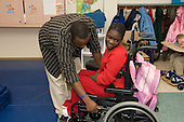 MR / Albany, NY.Langan School at Center for Disability Services .Ungraded private school which serves individuals with multiple disabilities.Teaching assistant (African-American) sets the wheelchair brakes for student. Girl: 10, African-American, cerebral palsy, expressive and receptive language delays.MR: And6; Wes2.© Ellen B. Senisi