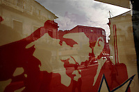 Street life is reflected in a shop window that has a poster of Fidel Castro posted inside in Havana, Cuba on 4 August 2006.