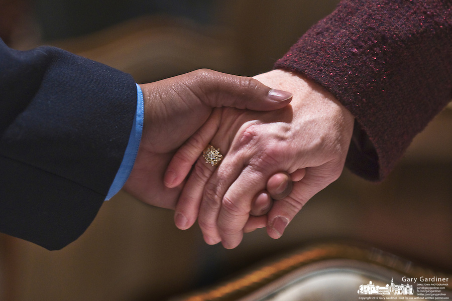 Two celebrants hold hands in unity during a prayer at the Westerville, Ohio, Martin Luther King Day celebration. Photo Copyright Gary Gardiner. Not be used without written permission detailing exact usage.