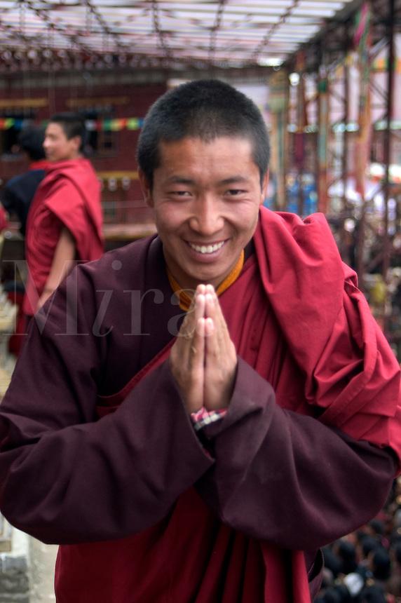 Tibetan Buddhist Monk gives the namaste greeting at the Katok Dorjeden Monastery - Kham, (eastern, Tibet), Sichuan, China