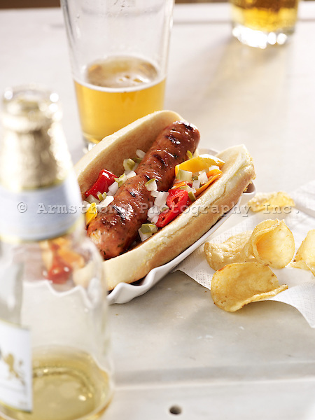 A grilled chicken-apple sausage on a hot dog bun, with onions, relish, and peppers. With beer glass and potato chips