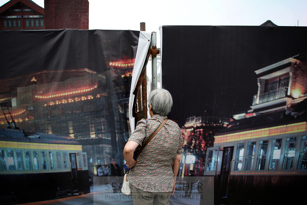"""CHINA. Beijing. An old  woman peers through a fence, trying to catch a glimpse of the new Qianmen shopping district. In recent years construction has boomed in Beijing as a result of the country's widespread economic growth and the awarding of the 2008 Summer Olympics to the city. For Beijing's residents however, it seems as their city is continually under construction with old neighborhoods regularly being razed and new apartments, office blocks and sports venues appearing in their place. A new Beijing has been promised to the people to act as a showcase to the world for the 'new' China. Beijing's residents have been waiting for this promised change for years and are still waiting, asking the question """"Where's the new Beijing?!"""". 2008"""