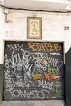 Tilework on a wall and graffiti on a shutter in Seville,Spain