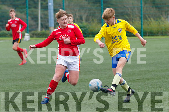 Niall Tadhg O'Brien for Killorglin AFC clears his lines as IUFC's Ben Egan tries to regain possession.