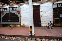 A child rides a tricycle outside a now closed restaurant next to one of Durban Deep Goldmine's old hostels on the outskirts of Johannesburg, South Africa.