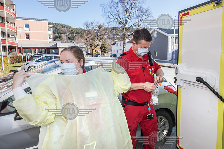Paramedics in the city of Drammen put on personal protective equipment (PPE) in order to transport patients during the Covid-19 , coronaviraus, pandemic.<br /> <br /> <br /> <br /> <br /> ©Fredrik Naumann/Felix Features