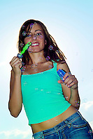 Sexy beautiful brunette wearing green tank top blowing bubbles in setting sun