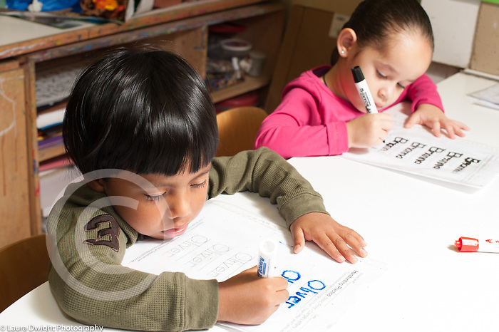 Education preschool 3-4 year olds boy and girl sitting side by side writing or tracing letters of their names