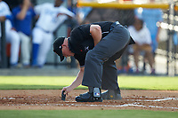 Home plate umpire Adam Pierce cleans home plate during the Appalachian League game between the Danville Braves and the Burlington Royals at Burlington Athletic Stadium on July 13, 2019 in Burlington, North Carolina. The Royals defeated the Braves 5-2. (Brian Westerholt/Four Seam Images)