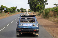 Senegal. On the road to Thies, a Renault 5 carries on its roof a ram tied up with a rope. 04.12.09  © 2009 Didier Ruef