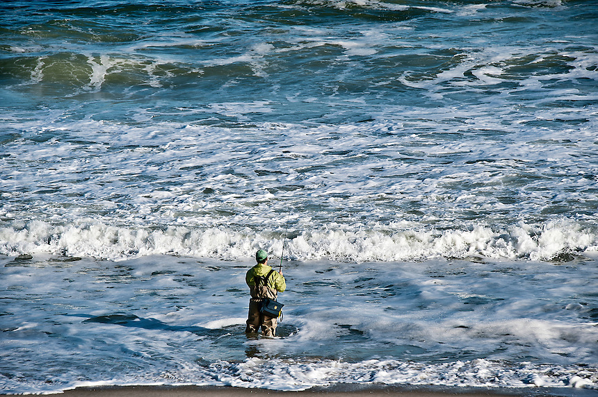 Man surf fishing from the beach, NJ, New Jersey, USA