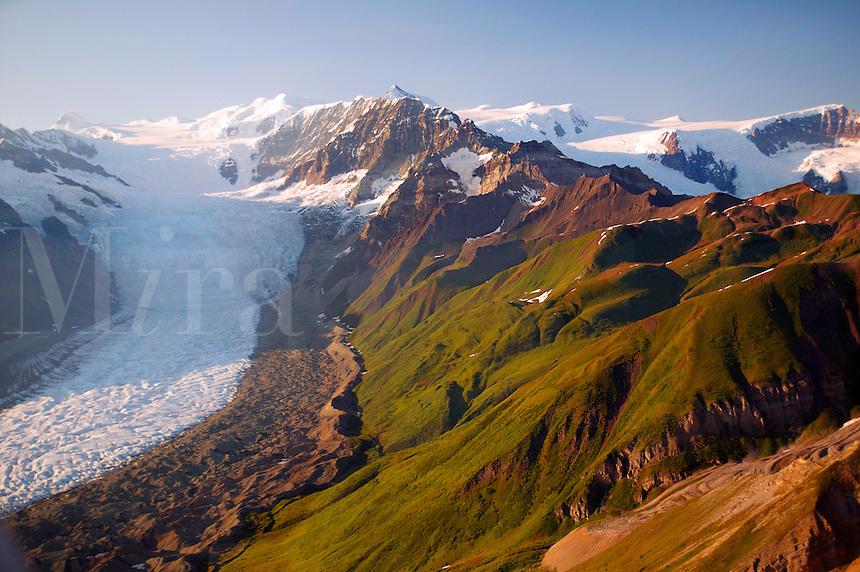 The green hills of Donoho Peak contrast with the Gates Glacier, Wrangell Saint Elias National Park and Preserve, Alaska