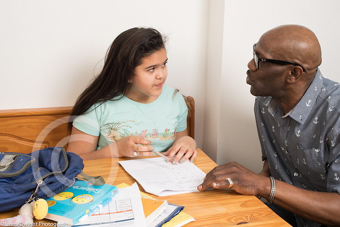 Girl, age 10, at home, doing homework at kitchen table, talking to or assisted by stepfather