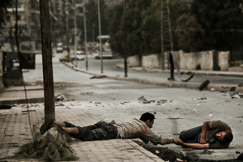 Free Syria Army soldiers crawled through the ground to reach him and pulled them towards a vehicle that rushed him to the hospital. It is not known if he survived. Three civilians were shot on this main road in the space of three hours by the same sniper. ..© Javier Manzano..