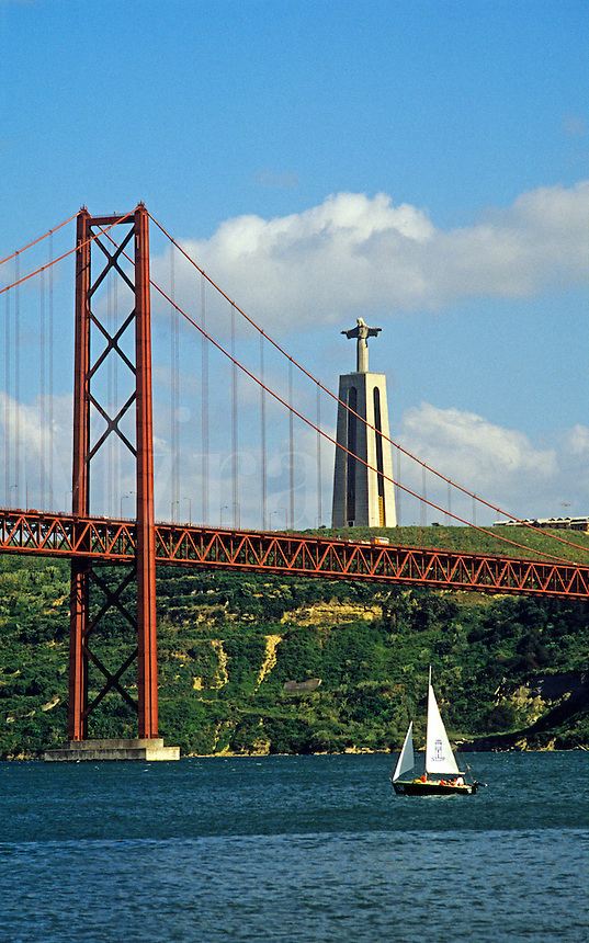 Portugal. Lisbon. Belem.  Ponte 25 de Abril, the original suspension bridge over the River Tagus, completed in 1966 it has an overall length of 2278 metres.  Statue of Christ in Majesty, a small replica of the one in Rio de Janeiro, in the background..