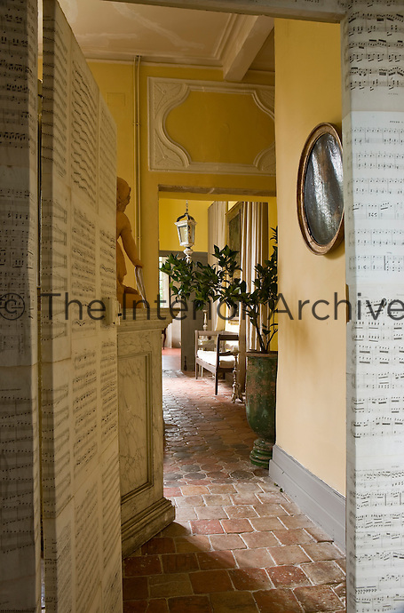 A view from the music room whose walls and door are lined with pages of musical notes down a tiled corridor with yellow ochre walls