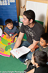 Education preschool 3-4 year olds male teacher working with group of children at circle time