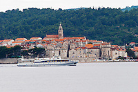 View across the sea on the town of Korcula on the island of the same name where Marco Polo was born. A ferry boat passing in front of the town. Korcula Island. Dalmatian Coast, Croatia, Europe.