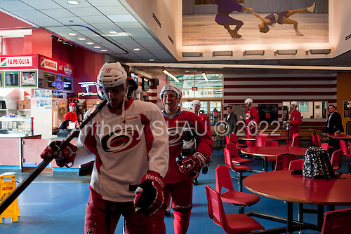 New York, New York<br /> November 10, 2011<br /> <br /> In shin, elbow and shoulder pads, hockey pants, gloves, jerseys and tennis shoes while carrying skates, sticks and helmets the Carolina Hurricanes, a professional hockey team, on their day off in New York between games against the New Jersey Devils and New York Rangers, take a bus for practice from Madison Square Garden at Chelsea Piers. <br /> <br /> As there are no locker rooms at Chelsea Piers the team dresses into their hockey equipment at Madison Square Garden. <br /> <br /> From Madison Square Garden the team takes an elevator and then boards a bus to Chelsea Piers like a bunch of Pee Wees climbing into their moms' mini vans. <br /> <br /> At Chelsea, the team climbs stairs or takes the elevator up to the sky rink. <br /> <br /> After practice, they return to the bus and Madison Square Garden, wet and sweaty to shower up.