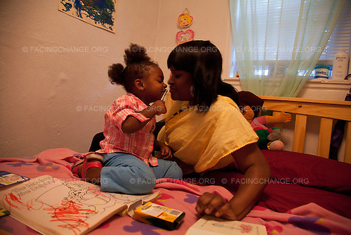 Boston, Massachusetts<br /> Aug 30, 2011<br /> <br /> Nichole Adams and her 2 year-old daughter, Khani, were among the One in fifty Americans who experience homelessness each year. Nichole lived in a rooming house and could no longer afford rent, even with her minimum wage job. She ended up in a shelter and was referred to Horizons for Homeless Children's preschool program for her daughter, Khani. Growing scientific evidence show that preschool homeless children are at risk for not developing crucial cognitive and brain development that occurs during this period in their lives. Programs like Horizons for Homeless Children (HHC) work at providing these children with a safe, play, and educational environment to promote that development.<br /> <br /> Caption: Parenting classes at HHC has inspired Nichole to read to Khani every night and spend time with her. As a result, Khani loves to read. However, at night both live in fear and anxiety as there have been 7 shootings and the murder of a three year old in their neighborhood over the past year.