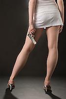 Lower body of Caucasian blonde woman facing away from camera holding handgun on black seamless<br />