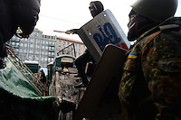 Rioters inside the barricades  holding police shileds and a baseball bate prepare for further  clashes.  Kiev. Ukraine