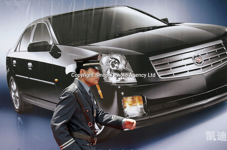 A guard walks past a Cadillac advertisement at the Auto Shanghai 2005 in Shanghai, China. Red Flag was renowned in China as the car for heads of state and high officials before western automakers edged in with their own luxury makes..