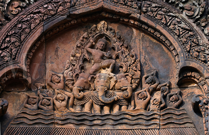 Bas relief in red sandstone of Indra riding his three headed elephant on the East Pediment of the North Library at Banteay Srei, 10th century Khmer architecture at Angkor Wat -  Siem Reap, Cambodia.