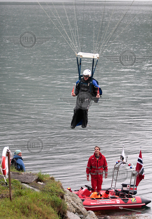 Espen Fadnes escapes a water landing, as a Red Cross volunteer looks on. World BASE Race held in Innfjorden, Norway, where BASE jumpers in wingsuits compete in flying down the mountain. The winner is called the World's Fastest Flying Human Being..©Fredrik Naumann/Felix Features.