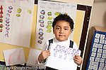 Education preschool proud boy holding up his drawing showing human figures and letters horizontal