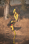 Cal Fire and local government crews from East Bay MUD and Moke Hill, along with airtankers and helicopters fight an 60 acre wildland fire near the Middle Bar Bridge over the Mokelumne River, Calaveras County, Calif...Moke Hill Fire Dept. firefighters connecting a hose line to support a wet line.