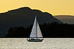 A sailboat on the Hudson River catches the last light of the day.