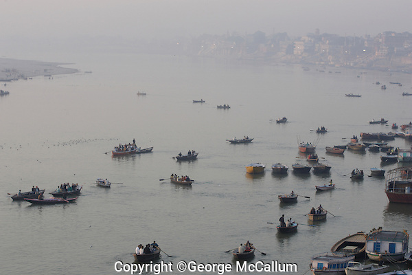 Rowing boats with tourists on Ganges river in morning smog,  Varanasi, India