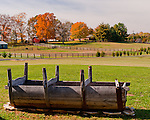An old trough displayed on the yard in front of Molon Lave Vineyards' winery building frames a picturesque fall view of neighboring farms and colorful trees showing fall foliage.