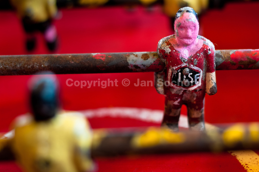 A table football player figure, with a painted red shirt, is seen inside the table football box on the street of Olmedo, a small village in the mountains of Ecuador, 27 June 2010. Table football, also known as futbolin in Latin America, is a widely popular table-top game in Ecuador. During the annual fairs, the rusty old outdoor-designed tables, fully ocuppied by excited children, may be found on all public places, particularly on the squares and in the parks. Human players use figures mounted on rotating bars to kick the small plastic ball into the opposing goal. Each team of 1 or 2 human players controls 4 rows on its side of the table. The game ends when one team scores a predetermined number of goals. In 2002, the International Table Soccer Federation (ITSF) was established to promote the sport of table football.