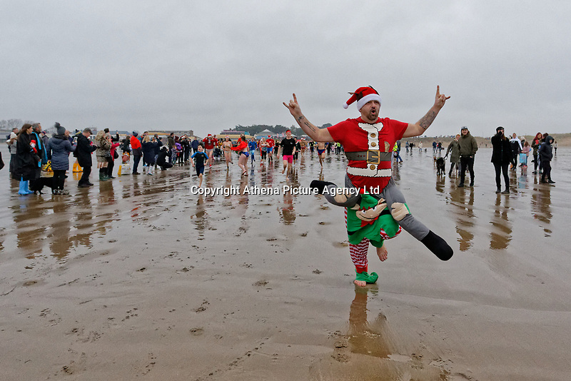 Pictured: A man in an elf fancy dress costume runs to the freezing cold see. Tuesday 25 December 2018<br /> Re: Hundreds of people take part in this year's Porthcawl Christmas Swim in south Wales, UK.