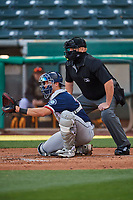 Cal Raleigh (29) of the Tacoma Rainiers on defense against the Salt Lake Bees while home plate umpire Tom Woodring makes the calls at Smith's Ballpark on May 13, 2021 in Salt Lake City, Utah. The Rainiers defeated the Bees 15-5. (Stephen Smith/Four Seam Images)