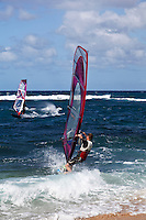 A windsurfer takes his board out to sea from Ho'okipa Beach, Maui. (NOTE: the man in the foreground is model released, the other is not.)