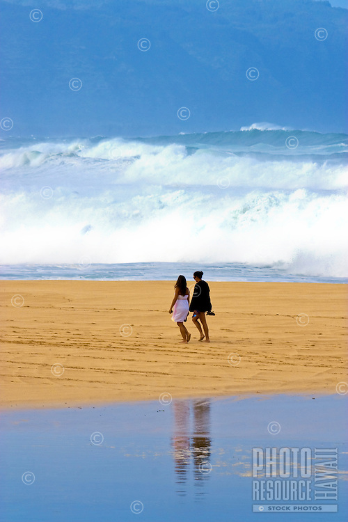 Two young women walk Waimea Bay beach with huge surf in the background and their reflections in a pool of water in the foreground