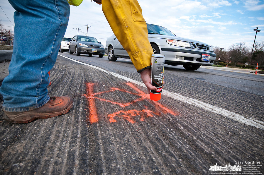 A worker sprays paint on a road surface to mark underground cables so construction crews will know where to dig to avoid damaging utility and communication cables beneath the roadway.