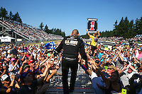 Aug. 3, 2014; Kent, WA, USA; NHRA top fuel dragster driver Tony Schumacher walks onto the stage as the number one qualifier during drivers introductions for the Northwest Nationals at Pacific Raceways. Mandatory Credit: Mark J. Rebilas-