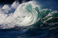 Large beautiful wave collides with backwash at the shore break of Waimea Bay on the North Shore of Oahu, Hawaii.