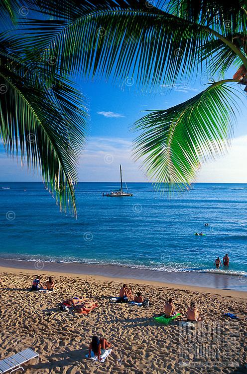 Palm trees frame the view of a catatmaran sailing towards the setting sun as tourists relax on beautiful Waikiki Beach, Oahu.